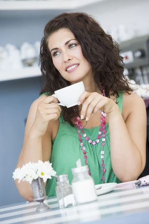 tea breaks: Young woman sitting at a table drinking tea