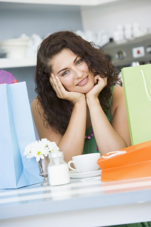 Young woman sitting at a table taking a break from shopping and drinking tea photo