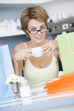 Young woman sitting at a table taking a break from shopping and drinking tea