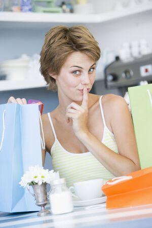 guilty pleasure: Joven mujer sentada en una mesa tomando un descanso de las tiendas y beber t�
