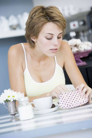 Young woman sitting at a table checking change purse