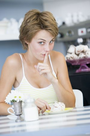 Young woman sitting at a table drinking tea and eating a sweet treat photo