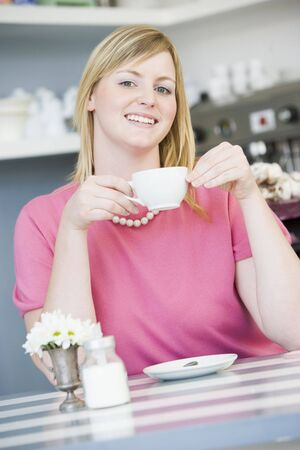 friends having tea series: Young woman sitting at a table drinking tea