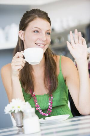 coffeebreak: Young woman sitting at a table drinking tea