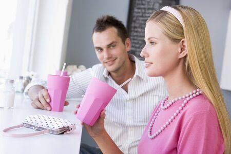 tomando refresco: Pareja joven con una bebida fr�a en una cafeter�a