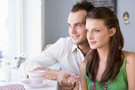 affectionate action: Pareja joven con una bebida fr�a en una cafeter�a