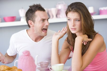exasperated: Young couple sitting at a table arguing