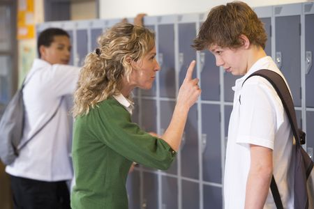 scolded: Female teacher reprimanding a male student Stock Photo