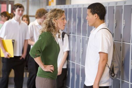 troubles: Female teacher reprimanding a male student Stock Photo