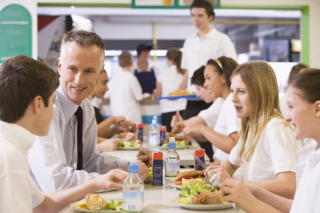 Students and teacher having lunch in dining hall photo