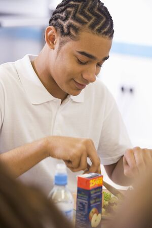 cornrows: Student having lunch in dining hall Stock Photo