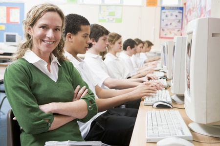 uniformly dressed: Students working on computer workstations with teacher