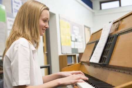 high school girl: Female student learning piano in classroom