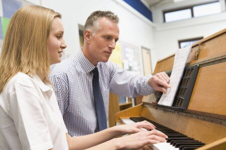Female student learning piano with teacher in classroom photo