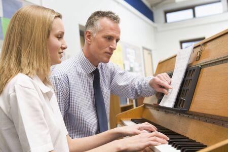 fortepian: Kobieta nauki ucznia z nauczycielem fortepianu w klasie