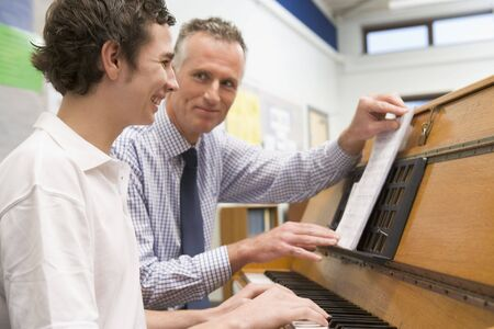 Male student learning piano with teacher in classroom photo