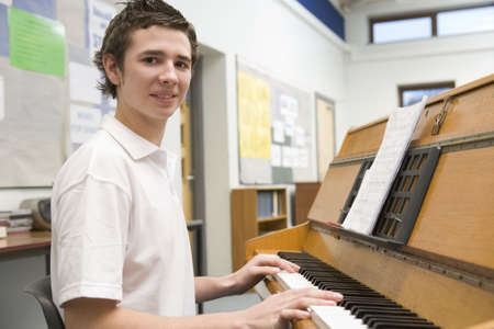 mid teens: Male student learning piano in classroom
