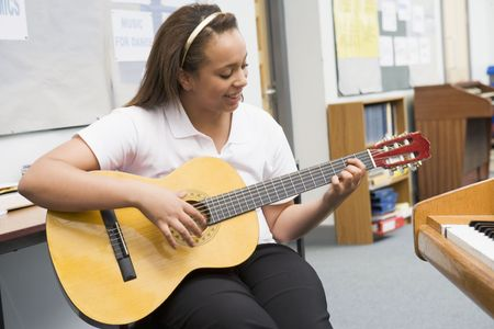 uniformly dressed: Female student learning guitar in classroom