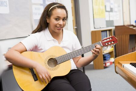 rehearse: Female student learning guitar in classroom