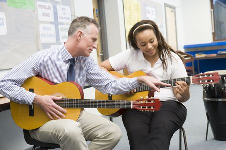 Female student receiving guitar lesson from teacher in classroom photo