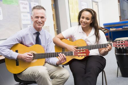 rehearse: Female student receiving guitar lesson from teacher in classroom