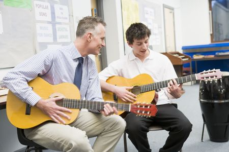 instruct: Male student receiving guitar lesson from teacher in classroom