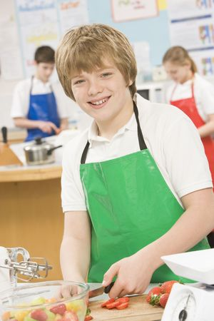 uniformly dressed: Male student slicing berries in cooking class Stock Photo