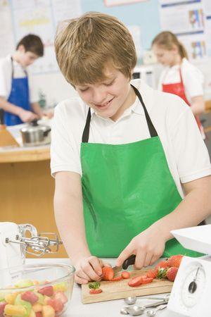 alumnos en clase: Estudiante masculino corte de bayas en clase de cocina  Foto de archivo