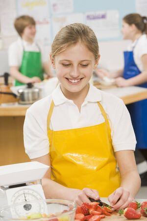 uniformly dressed: Female student slicing berries in cooking class