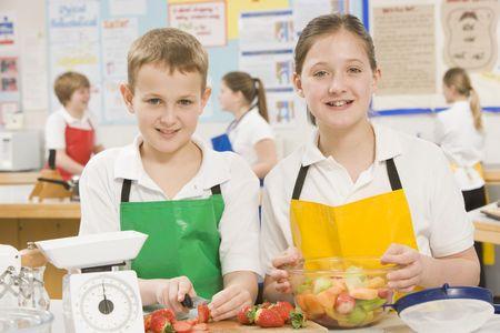 uniformly dressed: Male and female student preparing sliced fruit