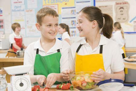 alumnos en clase: Masculino y femenino de los estudios la preparación de frutas en rodajas