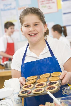 uniformly dressed: Female student holding a tray of tarts in cooking class