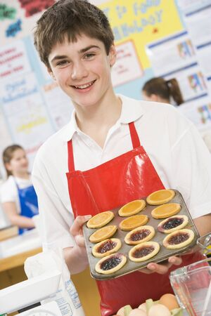Male student holding a tray of tarts in cooking class photo
