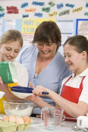 alumnos en clase: Los estudiantes en la preparación de ingredientes de cocina de clase con profesor