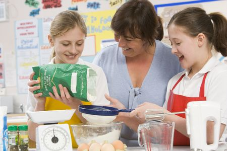 adult class: Students preparing ingredients in cooking class with teacher Stock Photo