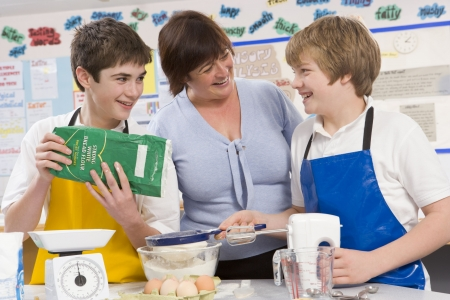 mentors: Students preparing ingredients in cooking class with teacher Stock Photo