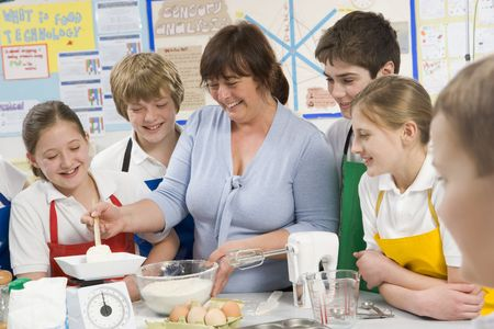 uniformly dressed: Students preparing ingredients in cooking class with teacher Stock Photo