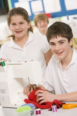 uniformly dressed: Male and female student using sewing machine