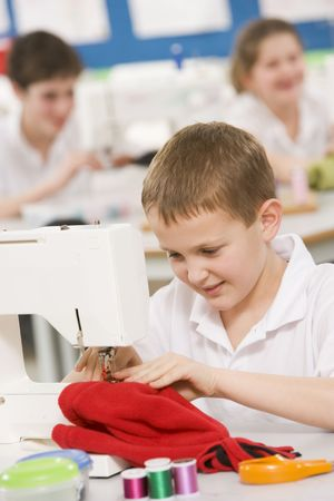 uniformly dressed: Male student using sewing machine Stock Photo
