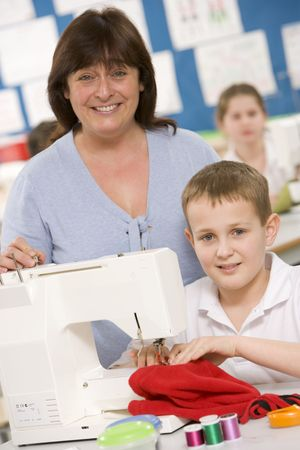 uniformly dressed: Male student using sewing machine with teacher