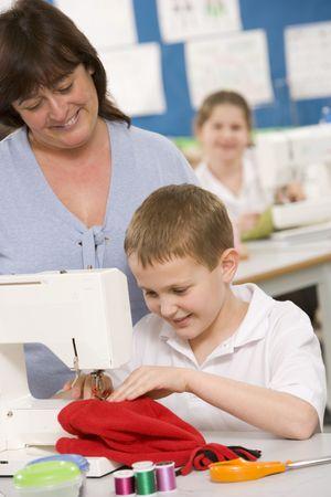 alumnos en clase: Estudiante masculino utilizando m�quina de coser con profesor