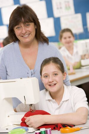 looking towards camera: Female student using sewing machine with teacher