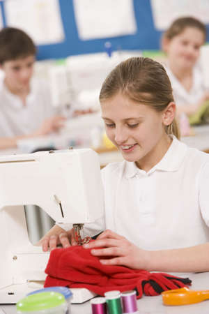 focused: Female student using sewing machine