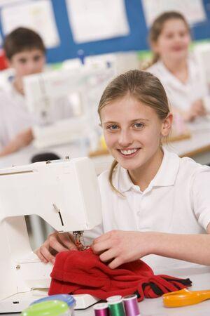 uniformly dressed: Female student using sewing machine