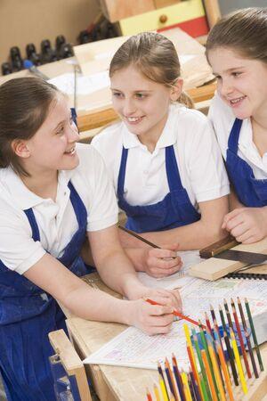 uniformly dressed: Female students learning woodworking Stock Photo