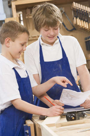 uniformly dressed: Male students reviewing woodworking plans Stock Photo