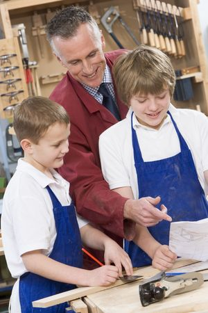 tweeny: Male students reviewing woodworking plans with teacher