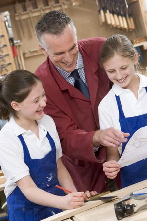 uniformly dressed: Female students reviewing woodworking plans with teacher