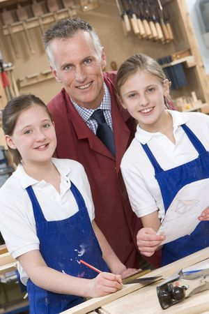 tweeny: Female students reviewing woodworking plans with teacher