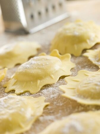Uncooked Spinach and Ricotta Ravioli on a floured surface photo